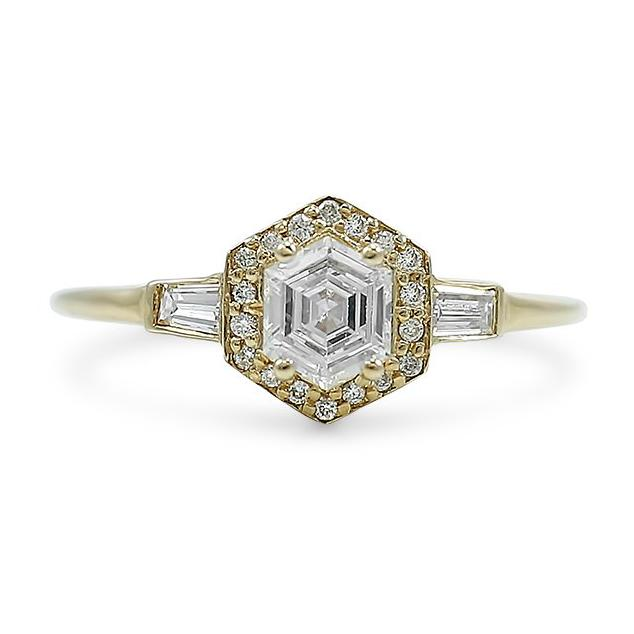Hexagon shaped diamond engagement ring with a yellow gold band and a diamond Halo with baguette side diamonds