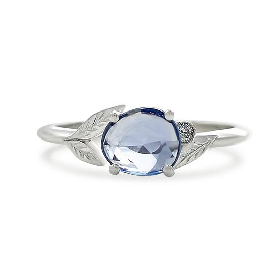 purplish-blue sapphire rose cut right hand ring with a bezel set white diamond and white gold band with leaves