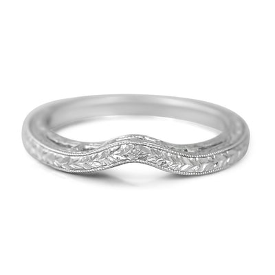 18k white gold baguette diamond wedding band with tons od engraving and a gentle contour