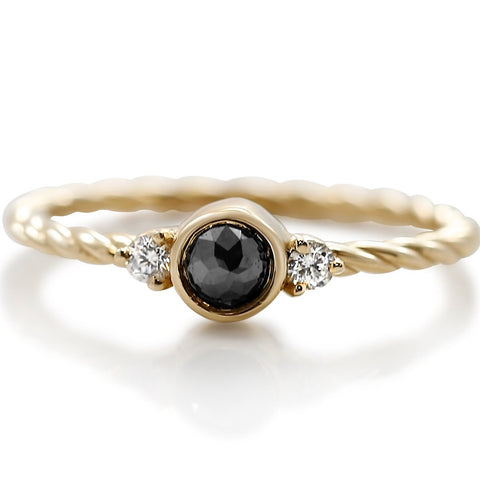 black and white diamond three stone stack ring with a yellow gold braided band