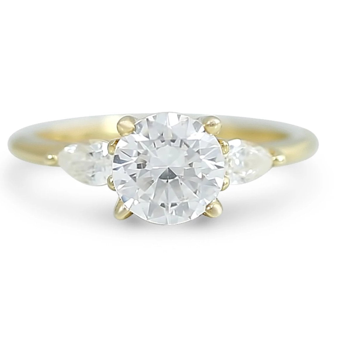 three stone ready to buy diamond engagement ring with pear shaped side stones prong set and available in 14k yellow, white, rose, or peach gold and platinum