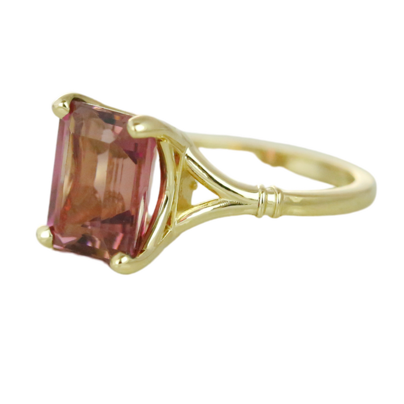 14k yellow gold emerald cut pink tourmaline prong set ring with a split shank band.