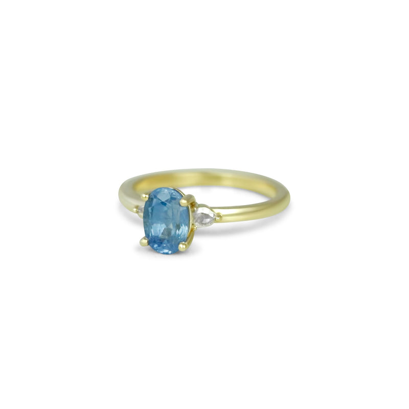 14k yellow gold three stone light blue sapphire engagement ring with a rose cut pear shaped diamond on each side