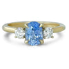 14k yellow gold three stone light blue oval sapphire engagement ring with petal prongs and two round brilliant cut diamondfs on each side.