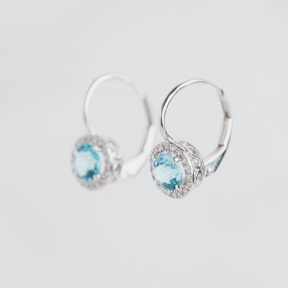 white gold blue topaz and diamond halo claw earrings