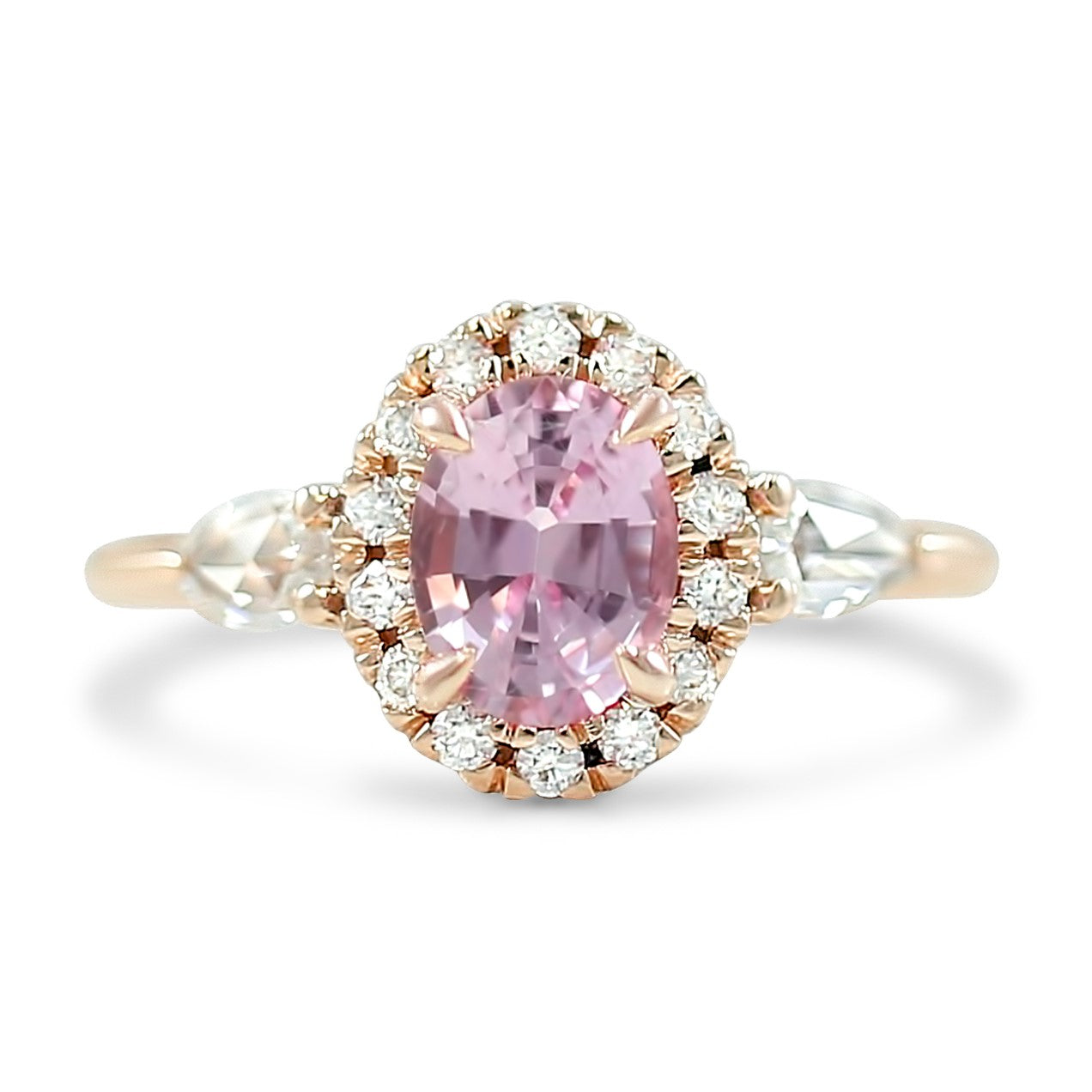 1.31ct pink oval sapphire set in 14k rose gold with a diamond halo and pear shaped diamond side stones