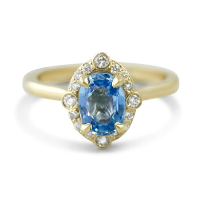 14k yellow gold oval light blue sapphire engagement ring with intricate diamond halo
