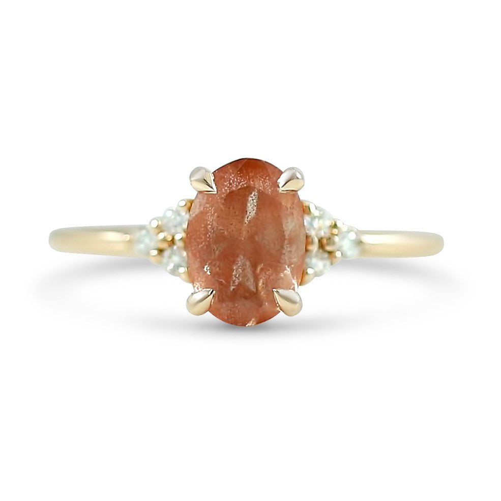 1.10ct oregon sunstone oval ready to ship engagement ring with clusters of diamonds on each side prong set in 14k peach gold