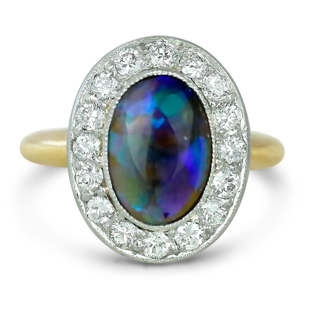 14k yellow and white gold cabochon cut oval opal estate ring with a bezel set diamond halo and milgrain details