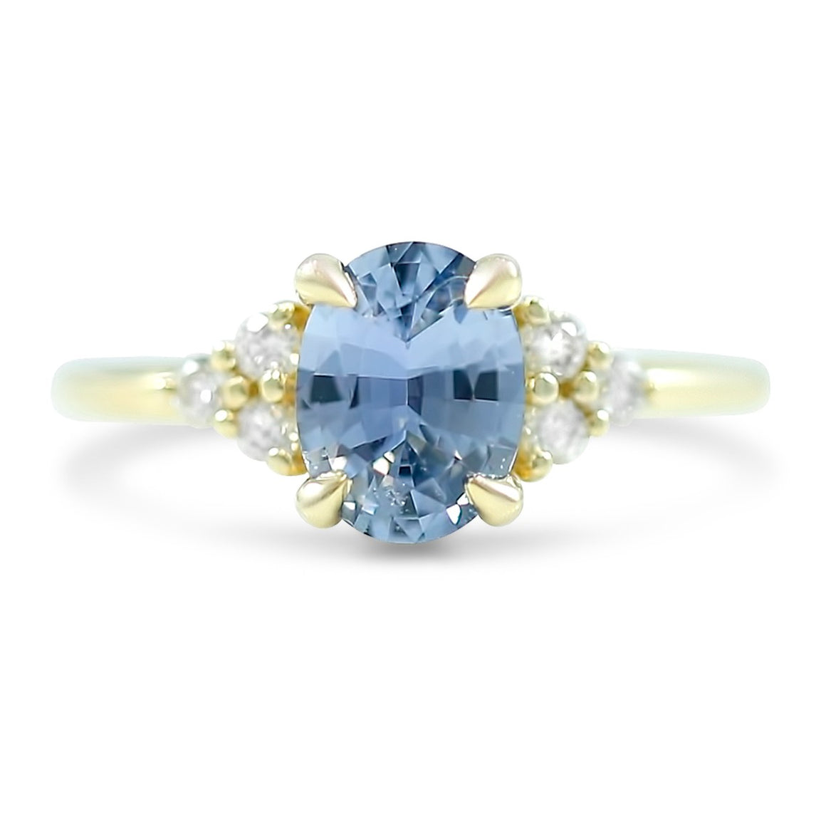 1.31ct light blue oval sapphire engagement ring with clusters of white diamonds on each side of center stone in 14k yellow gold