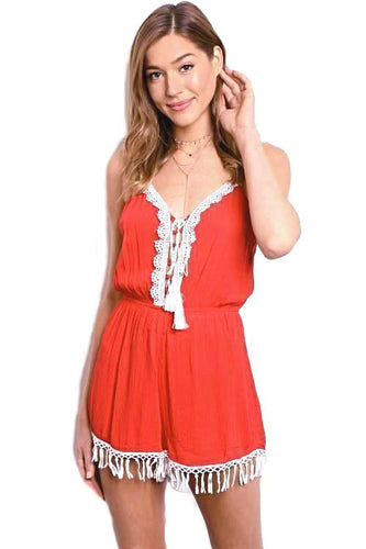 This red and white spaghetti strap woven romper has a contrast colored embroidered design along center front, gathered waist and tassel trim hem. - Shop  Canary Clothing