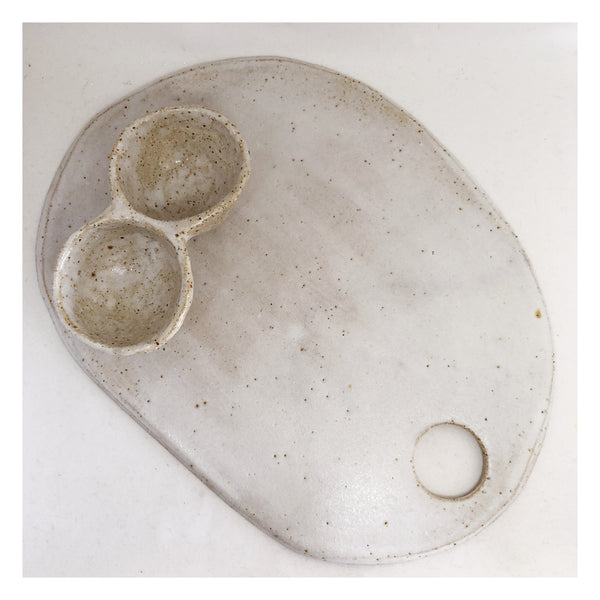 white speckled ceramic cheese board with pinch pot