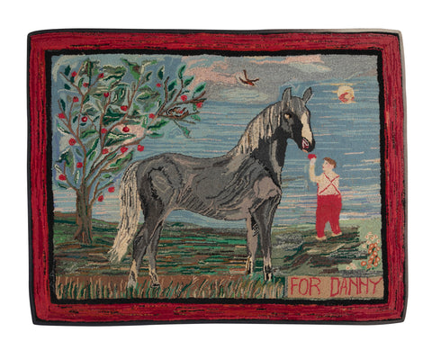 An Exceptional American Hooked Rug Depicting a Boy Feeding an Apple to a Horse