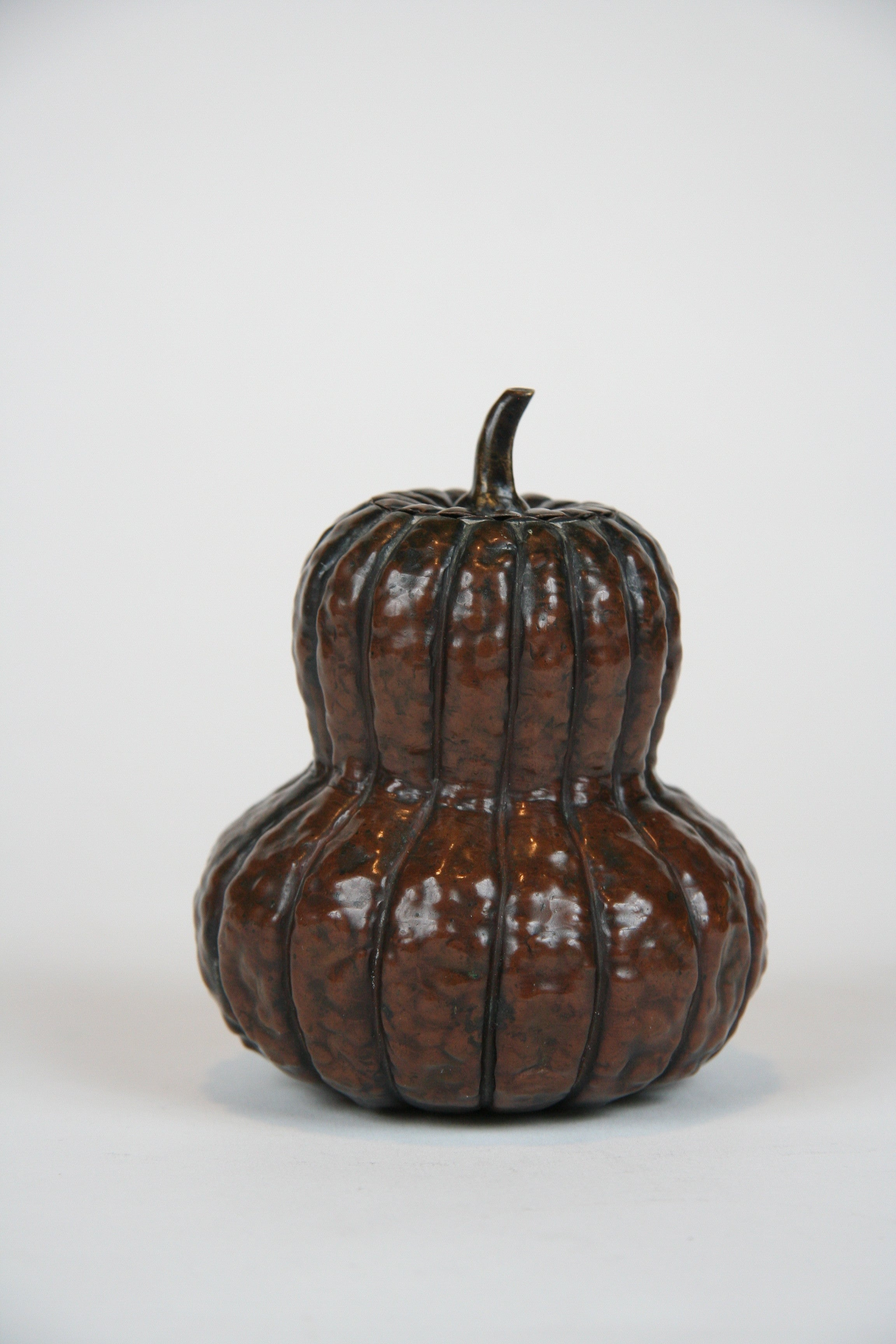 A Japanese Repousse Copper Scroll Weight in the Form of a Gourd