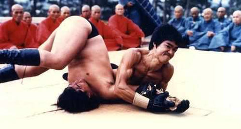 Bruce actually applies a sloppy, early modified armbar on poor Sammo Hung! With the first set of MMA gloves ever made we might add. Holy shit!