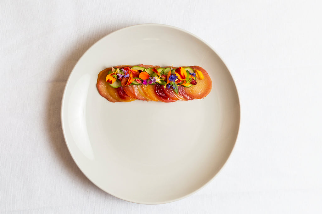 A white plate with a 'line' of baked fruits garnished with flowers sits on a white table.