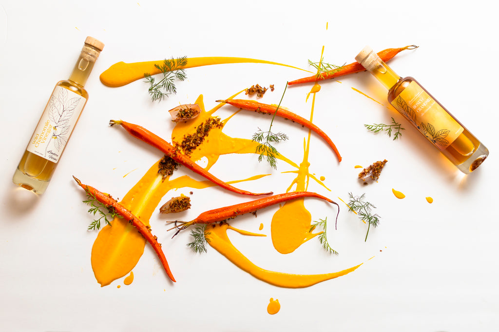 On top of a white background, orange colored carrot and chamomile puree is splattered underneath roasted carrots and bottles of Lindera Farms Wild Chamomile Vinegar and Honey and Chamomile Syrup.