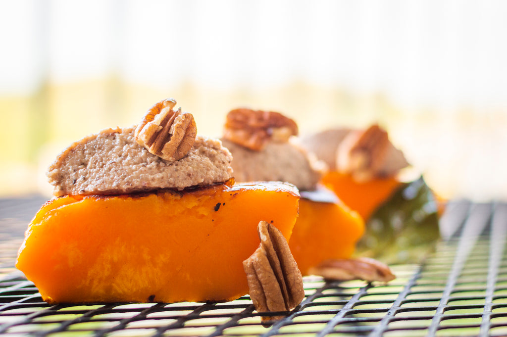 Butternut squash topped with a shiitake and pecan pesto sitting on a black, grated table.