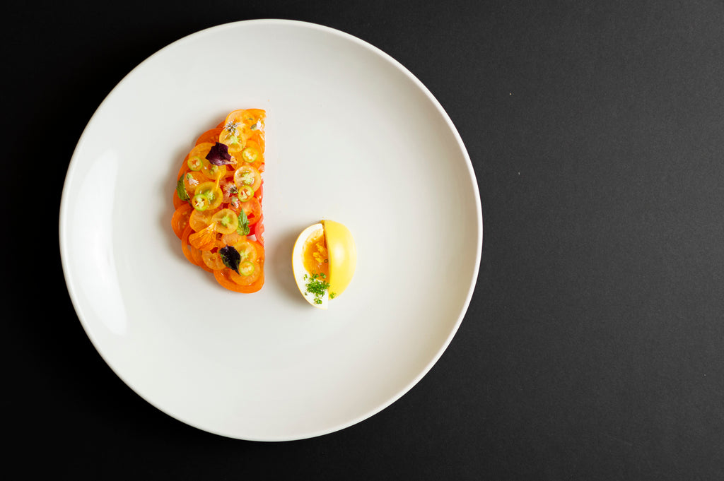 Heirloom cherry tomato salad shaped into a semi circle with a cut golden egg on a white plate sitting on a black background.