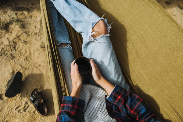 Coffee in a hammock camping. Flannel, Birkenstocks and ripped jeans.
