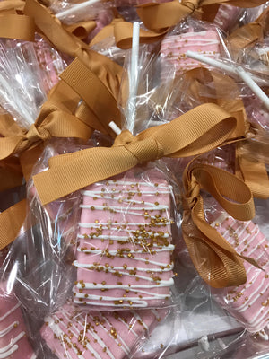 Pink Chocolate Covered Rice Krispie Treats with White Drizzle and Gold Sprinkles