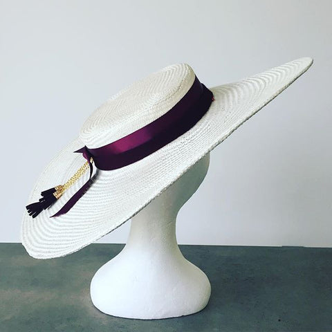 White wide brim hat with maroon trim via Maker Millinery