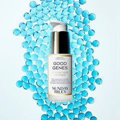 A Good Genes Glycolic frosted glass bottle with gold cap and white pump in a 30 mL bottle lay down on light blue marbles.