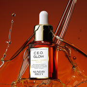 C.E.O. Glow Face Oil in a orange gradient glass bottle with silicon dropper with splashes of oil in the background.
