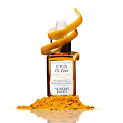 C.E.O. Glow Face Oil in a orange gradient glass bottle with an orange slice wrapped around the silicon dropper top and orange powder in front of bottle..