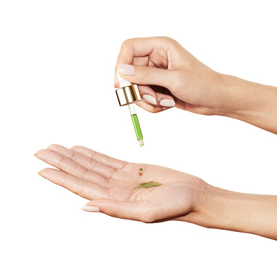 Hand holding dropper, dispensing green UFO face oil onto palm, cherry red manicure