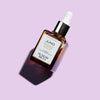 light violet background, Juno Superfood face oil glass bottle