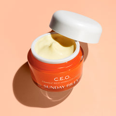 Pastel orange background, open CEO moisturizer jar, light yellow moisturizer cream
