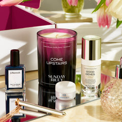 Come Upstairs Candle on reflective glass with Good Genes glycolic, ICE Ceramide moisturizing cream (both mini deluxe versions) along with J Hannah nail polish and Crave vibrator