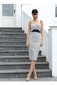 Woman standing near stairs wearing a 50s Style Black and White Wiggle Dress with Cutout and Black Spaghetti Straps