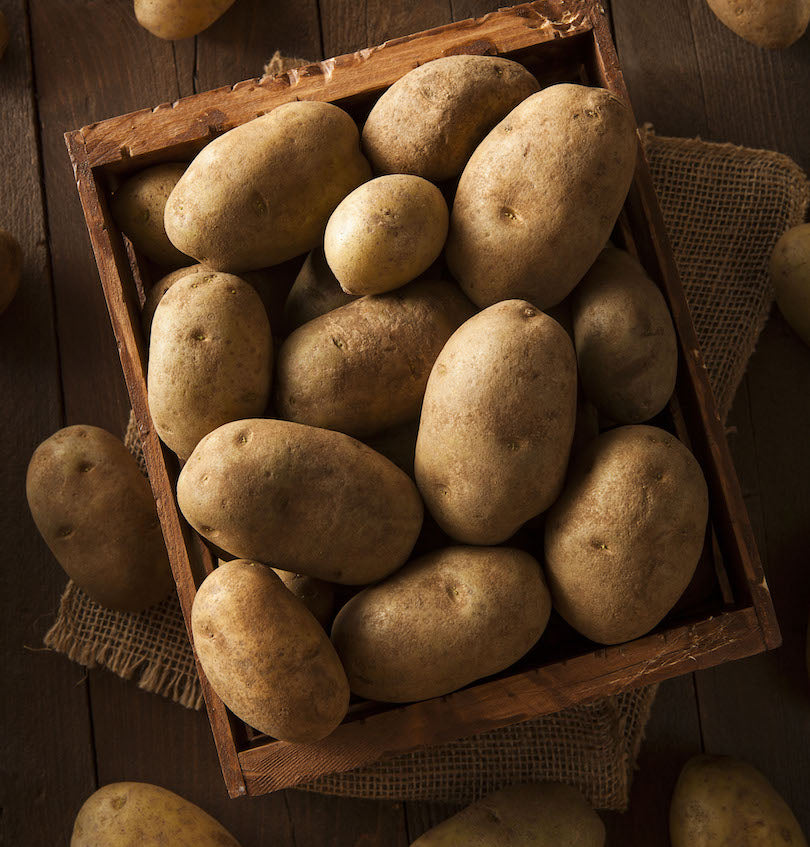 overhead shot of potatoes in a wooden box