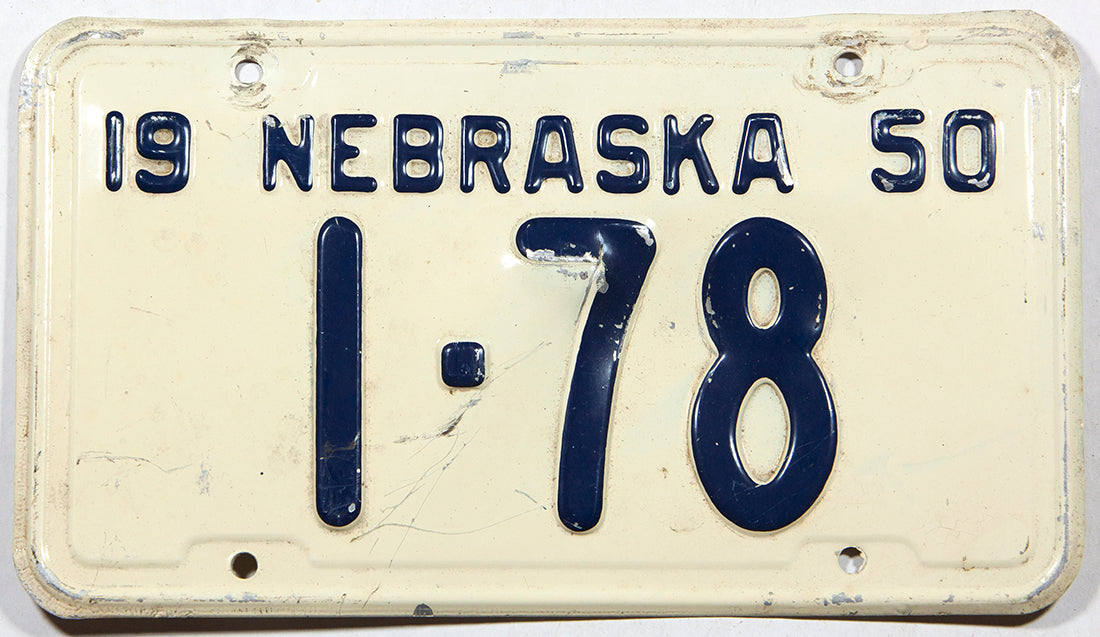 An antique 1950 Nebraska passenger car license plate in very good condition with bends in the metal