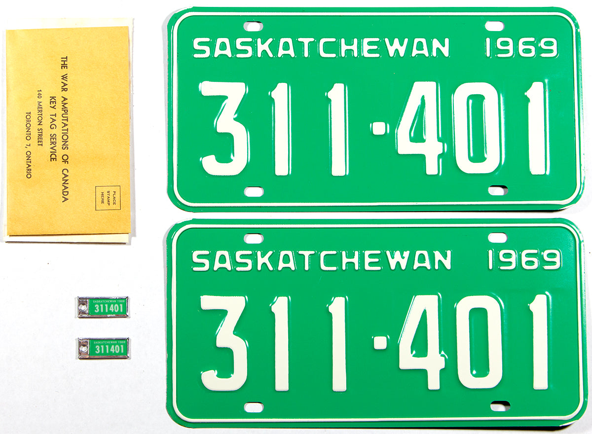 A near mint pair of 1969 Saskatchewan Canada license plates still with their matching War Amputations key tags