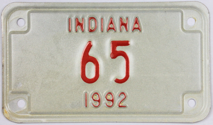 A NOS 1992 Indiana motorcycle license plate with a low DMV registration number. The 92 IN plate is in Excellent Minus condition.