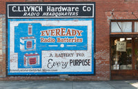 A premium quality print of a cool advertisement for Eveready Radio Batteries on the side of a hardware store painted on the bricks