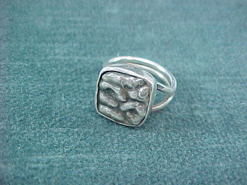 Signed studio sterling ring with bezel set repousse plaque