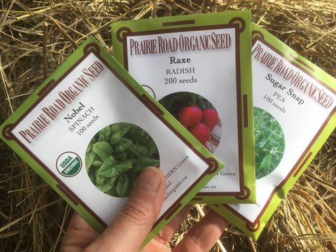 Cold tolerant seed packets of spinach, radish and peas ready for planting at Prairie Road Organic Seed