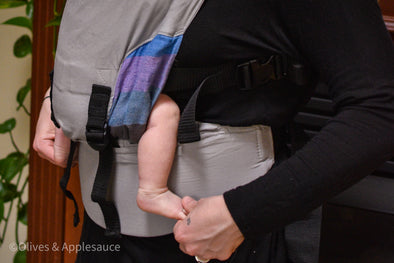 "Close up of the Olives and Applesauce Olympia Baby Carrier highlighting the perfect ergonomic ""m"" seat on a newborn"
