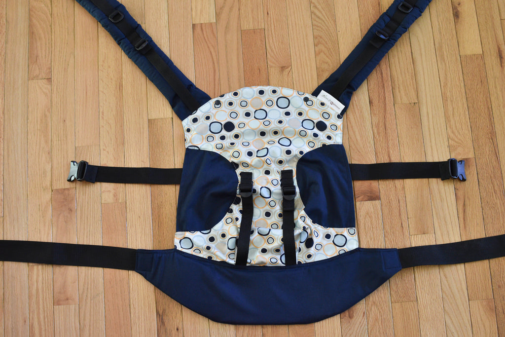 "Olives and Applesauce Olympia Carrier laid flat on the floor. The print, Cobblestone, is cut in an hourglass shape with navy twill semi-circle ""cut outs"" completing the panel. It has matching navy shoulders straps and waistband"