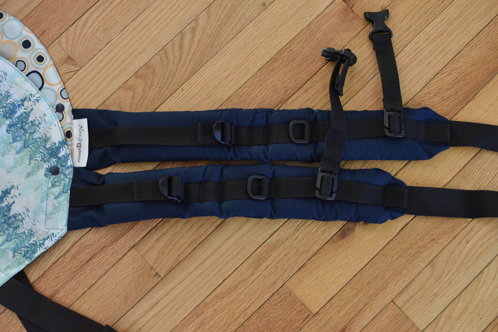 "The shoulders straps on an Olives and Applesauce Olympia carrier and Hydrogen carrier laying side by side. The Olympia has shoulder straps nearly 3"" longer."