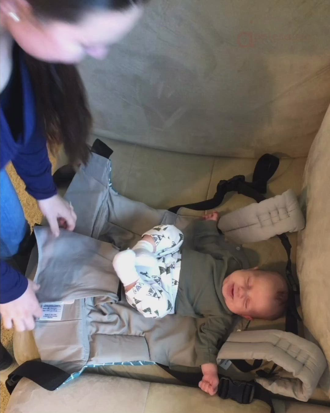 Video demonstration of the Olives and Applesauce Hydrogen carrier. A mother buckles her baby into the harness, then puts the carrier on