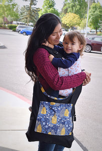 A pacific islander woman is looking down at her smiling toddler son on her front. She is wearing him in Sly as a Fox Hydrogen carrier (a white background with orange foxes all over, with black shoulder straps and body panel), with a Beez Neez crossbody bag over the carrier (a reversible bag with the black side showing and the pocket with bees neez print on the front- a blue background with yellow bee hives, small bees, and white ferns)