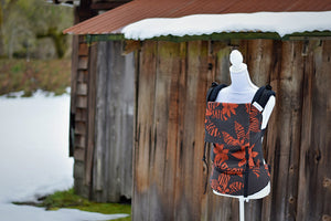 Crush has a black background with red/orange tropical flowers, some with animal print on the petals. The wrap is used on the body panel and waistban. It is paired with black shoulder straps.