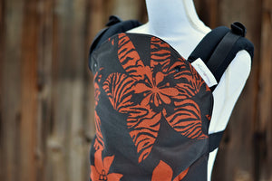 Olives and Applesauce Crush has a black background with red/orange tropical flowers, some with animal print on the petals. The wrap is used on the body panel and waistban. It is paired with black shoulder straps.