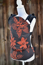 Load image into Gallery viewer, Olives & Applesauce Crush has a black background with red/orange tropical flowers, some with animal print on the petals. The wrap is used on the body panel and waistban. It is paired with black shoulder straps.
