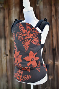 Olives & Applesauce Crush has a black background with red/orange tropical flowers, some with animal print on the petals. The wrap is used on the body panel and waistban. It is paired with black shoulder straps.